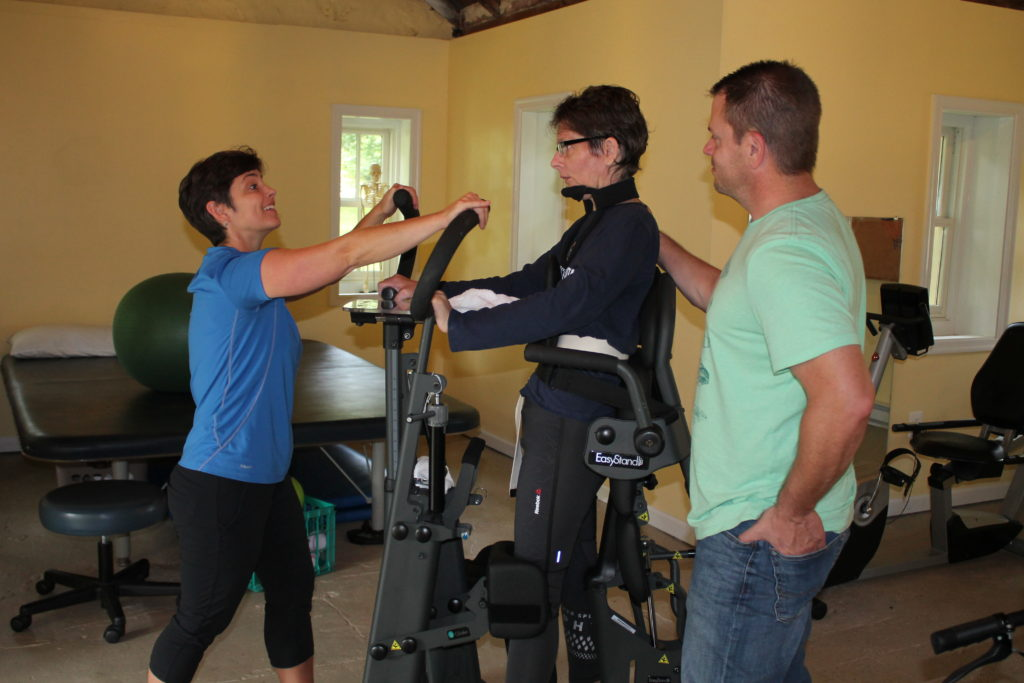 Helen, our expert clinician, helping a client on specialized equipment